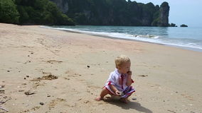 Girl in Ukrainian costume embroidery on beach. Little girl in the national Ukrainian costume embroidery found stone walking on the beach stock footage