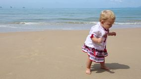 Girl in Ukrainian Costume Embroidery on Beach. Little girl in the national Ukrainian costume embroidery found stone walking on the beach stock video footage