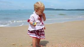 Girl in Ukrainian Costume Embroidery on Beach. Little girl in the national Ukrainian costume embroidery walking on the beach stock footage