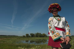 A girl in Ukrainian embroidery with a wreath on her head by the lake in a meadow among the flowers. National clothes - a girl in Ukrainian embroidery with a Stock Photo