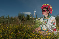 A girl in Ukrainian embroidery with a wreath on her head by the lake in a meadow among the flowers. National clothes - a girl in Ukrainian embroidery with a royalty free stock photo