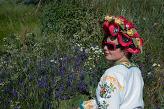 A girl in Ukrainian embroidery with a wreath on her head by the lake in a meadow among the flowers. National clothes - a girl in Ukrainian embroidery with a stock photos