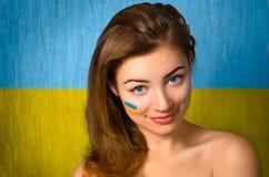 Girl and Ukrainian flag. Girl with Ukrainian flag on her cheek stock photo
