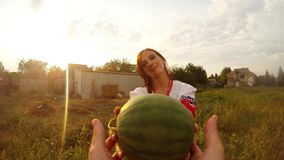 A girl in Ukrainian folk clothes gives a watermelon to a person by the camera, a first person view stock footage