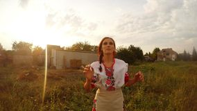 A girl in Ukrainian folk clothes throws watermelon at the camera and catches a flying watermelon from behind the camera. Collection, a girl in a traditional stock video