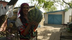 Girl in Ukrainian folk clothes with a watermelon in hands, on a background of drying clothes in a rural yard posing on the camera. Collection, a girl in a stock footage