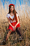 Girl in Ukrainian national costume smiling sitting in the reeds Stock Images