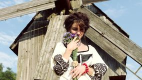 The girl in the Ukrainian style with flowers poses for the camera. The girl in the Ukrainian style with flowers poses for the camera on the background of the stock video