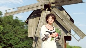 The girl in the Ukrainian style with flowers poses for the camera. A girl in Ukrainian style with flowers walks and turns on camera against the background of an stock video