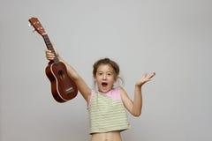 Girl with ukulele guitar Stock Images
