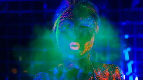 Girl in ultraviolet light blows green fluorescent powder with palm