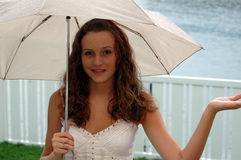 Girl with umbrella. A pretty teen girl in the rain under an umbrella with the palm of her hand outside catching rain stock photo