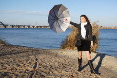 Girl with the umbrella. Young pretty girl with an umbrella in the autumn beach Stock Photography
