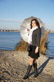 Girl with the umbrella. Young pretty girl with an umbrella in the autumn beach Stock Photos