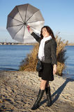 Girl with the umbrella. Young pretty girl with an umbrella in the autumn beach Royalty Free Stock Photos