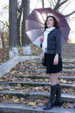 Girl with umbrella. Beautiful girl with an umbrella on the steps of an abandoned ladder Stock Photo