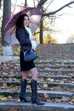 Girl with umbrella. Beautiful girl with an umbrella on the steps of an abandoned ladder Royalty Free Stock Photography