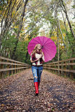 Girl with umbrella. A pretty young woman under an umbrella walking on a path in autumn looking up. Fall weather royalty free stock image
