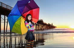 Girl with umbrella. A young girl standing on a sunny beach with a colorful umbrella Stock Photography