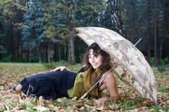 Girl with umbrella. Lying at autumn park and smiling Royalty Free Stock Photo