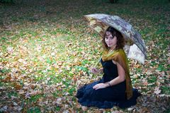 Girl with umbrella. Sitting on grass at autumn park Stock Photos