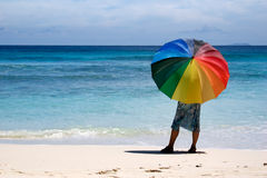Girl with umbrella. On coastline stock image