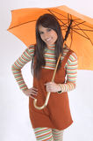 Girl and umbrella. Pretty girl with orange umbrella in her hand Royalty Free Stock Photography