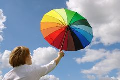 Girl with umbrella. Young woman wearing white blouse holding multicolored umbrella up against the sky Stock Photo