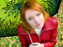 Girl with umbrella. Beautiful red girl in leather jacket with umbrella Stock Images