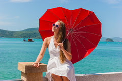 Girl with an umbrella against the sea Stock Photo