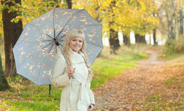 The girl with an umbrella in autumn park Stock Image
