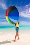 Girl with umbrella on beach. A girl with a colorful umbrella on the beach Stock Image