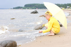 Girl with umbrella on a beach Royalty Free Stock Photography