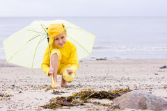 Girl with umbrella on a beach Stock Image