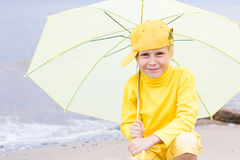 Girl with umbrella on a beach Stock Images