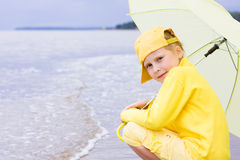 Girl with umbrella on a beach Stock Photos