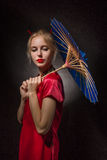 Girl with umbrella. Beautiful girl in asian costume with umbrella on black background Stock Photo