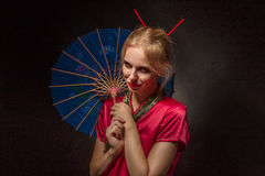Girl with umbrella. Beautiful girl in asian costume with umbrella on black background Royalty Free Stock Image