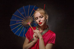 Girl with umbrella. Beautiful girl in asian costume with umbrella on black background Royalty Free Stock Photos