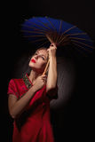 Girl with umbrella. Beautiful girl in asian red dress with umbrella on black background Stock Images