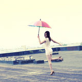 Girl with an umbrella. Beautiful attractive girl with an umbrella flies from the roof Stock Photography