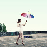 Girl with an umbrella. Beautiful attractive girl with an umbrella flies from the roof Royalty Free Stock Photo