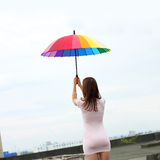 Girl with an umbrella. Beautiful attractive girl with an umbrella flies from the roof Royalty Free Stock Image