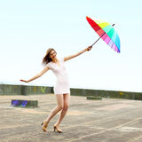 Girl with an umbrella. Beautiful attractive girl with an umbrella flies from the roof Stock Photos