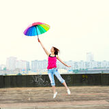 Girl with an umbrella. Beautiful attractive girl with an umbrella flies from the roof Royalty Free Stock Images