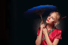 Girl with umbrella. Beautiful girl in japanese red costume with umbrella on black background, toned image Royalty Free Stock Photos