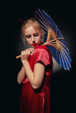 Girl with umbrella. Beautiful girl in japanese red costume with umbrella on black background, toned image Royalty Free Stock Image
