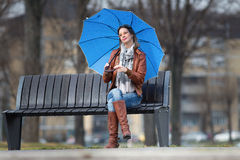 Girl with umbrella on the bench Stock Photography
