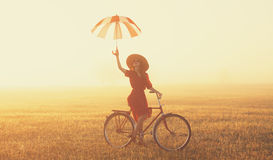 Girl with umbrella on a bike Royalty Free Stock Photography