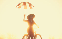 Girl with umbrella on a bike Royalty Free Stock Images